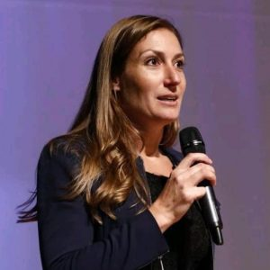 Isabel van Bemmelen with a microphone on a purple background